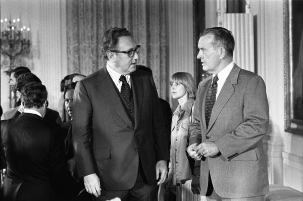 Secretary of State Henry Kissinger and Deputy Secretary of Defense William Clements attend a signing ceremony for the Treaty on Underground Nuclear Explosions for Peaceful Purposes (PNE) between the US and the USSR in the White House East Room, 5/28/1976.