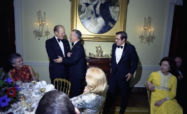 President Gerald Ford, Secretary of Defense Donald Rumsfeld, and Deputy Secretary of Defense William Clements attend a dinner for the Secretary of Defense, Service Secretaries, Joint Chiefs of Staff, and Commanders or the Unified Commands in the White House State Dining Room, 12/11/1976.