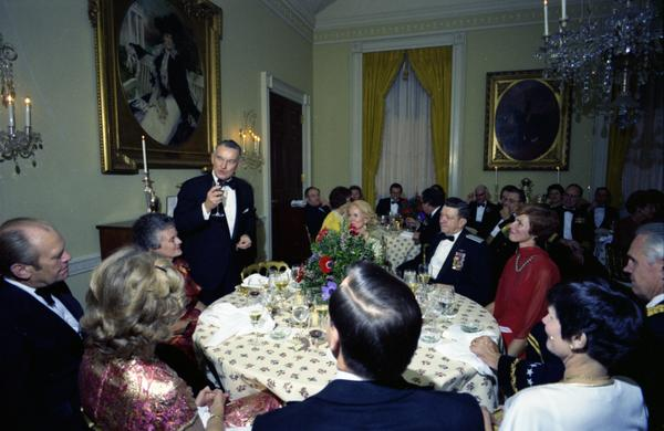 President Ford, Betty Ford, Donald Rumsfeld, Brent Scowcroft, William Clements, Martin Hoffman, Thomas Reed, George S. Brown, David Jones, Bernard Rogers, Louis Wilson, John Hennesey, Daniel James, Jr., Russell Daugherty, Robert Huyser, Anthone McAuliffe, James Holloway, Eugene Siler, Isaac Kidd, Maurice Weisner, William Hyland, and their spouses attend a dinner for the Secretary of Defense, Service Secretaries, Joint Chiefs of Staff, and Commanders or the Unified Commands in the White House State Dining Ro
