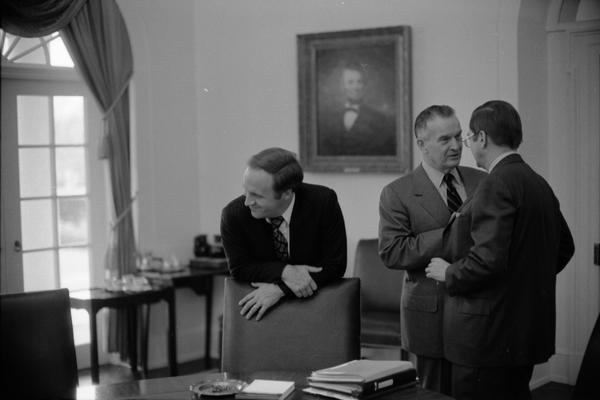 White House Chief of Staff Richard Cheney, Deputy Secretary William Clements, and Secretary of Defense Donald Rumsfeld speak prior to a National Security Council Meeting in the White House Cabinet Room, 12/15/1976.