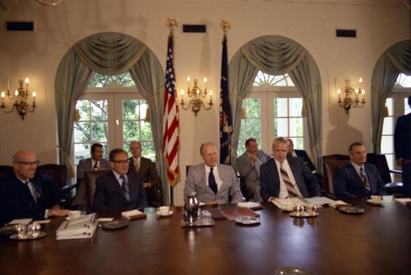President Gerald Ford, Henry Kissinger, James Schlesinger, Robert Ingersoll, William Clements, Brent Scowcroft, Robert Hartmann, and John Marsh attend a National Security Council meeting in the White House Cabinet Room, 8/10/1974.