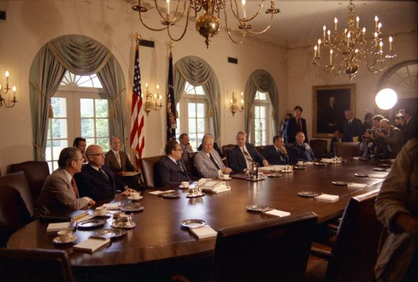 Gerald R. Ford, Henry Kissinger, James Schlesinger, Robert Ingersoll, William Clements, George Brown, William Colby, Brent Scowcroft, Kennedy, Donald Rumsfeld, Robert Hartmann, John Marsh, and media attend a National Security Council meeting in the White House Cabinet Room, 8/10/1974.