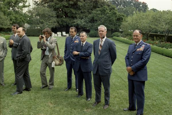 General David Jones, Assistant Secretary of Defense William Clements, Secretary Schlesinger, General George Brown, and photographers attend Brent Scowcroft's promotion ceremony to Lieutenant General in the White House Rose Garden, 9/5/1974.