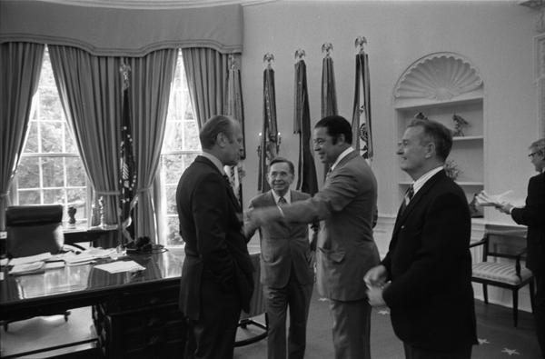 President Gerald Ford, Assistant Secretary of Defense William Clements, Representative Carl Albert (OK), and Senator Edward Brooke (MA) discuss the Combined Federal Campaign in the Oval Office, 9/17/1974.