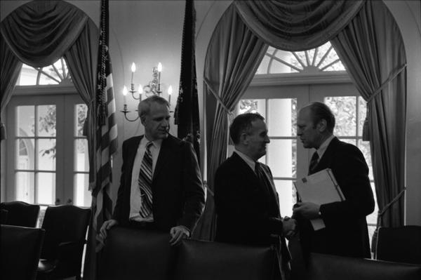 President Gerald Ford, Secretary of Defense James Schlesinger, and Deputy Secretary of Defense William Clements speak prior to a National Security Meeting in the White House Cabinet Room, 10/18/1974.