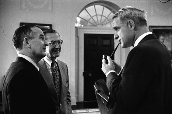 CIA Director William Colby, Deputy Secretary of Defense William Clements, and Secretary of Defense James Schlesinger speak prior to a National Security Meeting in the White House Cabinet Room, 10/18/1974.