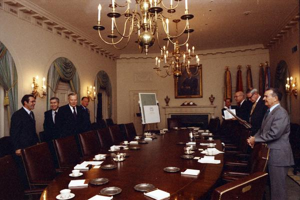James Schlesinger, General George Brown, Fred Iklé, William Colby, Robert Ingersoll, U. Alexis Johnson, William Clements, Jan Lodal, Brent Scowcroft, and Donald Rumsfeld speak prior to a National Security Meeting in the White House Cabinet Room, 12/2/1974.