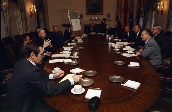 President Gerald Ford, James Schlesinger, General George Brown, Fred Iklé, William Colby, Robert Ingersoll, U. Alexis Johnson, William Clements, Jan Lodal, Brent Scowcroft, and Donald Rumsfeld attend a National Security Meeting in the White House Cabinet Room, 12/2/1974.