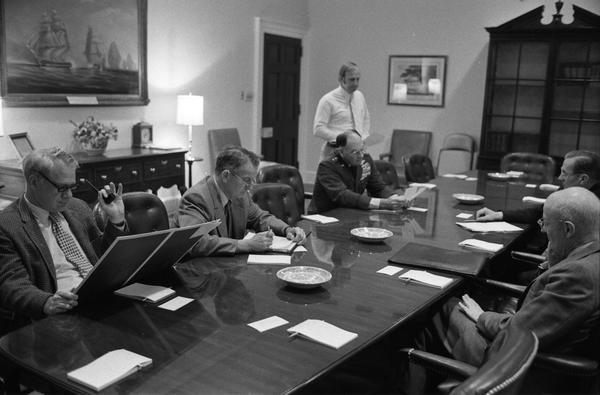 James Schlesinger, General George S. Brown, William Colby, Robert Ingersoll, and William Clements speak prior to a National Security Meeting in the White House Roosevelt Room, 4/28/1975.